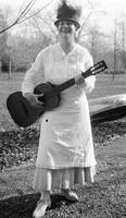 Woman standing outdoors holding guitar