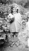 Elizabeth (Biz) Schoonover as a child posing with vegetable at Bushkill