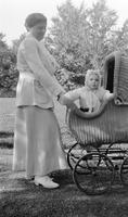 Elizabeth (Biz) Schoonover as an infant being pushed in wicker baby carriage