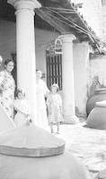 Women and children standing in front of dwelling in Cuba near tinajónes